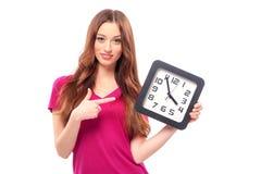 Muchacha sonriente que sostiene un reloj grande Imagenes de archivo