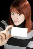 Muchacha sonriente que sostiene una tarjeta en blanco Imagenes de archivo