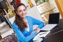 Muchacha sonriente que tiene un descanso para tomar café y que trabaja en un ordenador Imagen de archivo libre de regalías