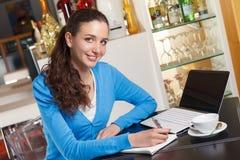 Muchacha sonriente que tiene un descanso para tomar café y que trabaja en un ordenador Fotos de archivo libres de regalías