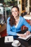 Muchacha sonriente que tiene un descanso para tomar café y que trabaja en un ordenador Foto de archivo libre de regalías