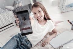 Muchacha sonriente que tiene una llamada de su amigo Foto de archivo libre de regalías