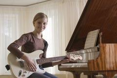 Muchacha sonriente que toca la guitarra Fotos de archivo