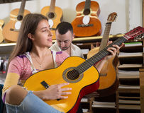 Muchacha sonriente que toca la guitarra acústica Imágenes de archivo libres de regalías