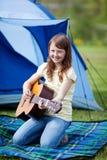 Muchacha sonriente que toca la guitarra contra la tienda Foto de archivo libre de regalías