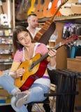Muchacha sonriente que toca la guitarra profesional Imagen de archivo libre de regalías