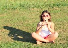 Muchacha sonriente que toca una flauta Imágenes de archivo libres de regalías