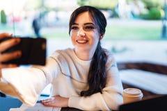 Muchacha sonriente que toma el selfie con sus manos para las redes sociales mientras que se sienta en caf? Retrato de la mujer jo imágenes de archivo libres de regalías