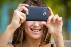 Muchacha sonriente que toma la foto con smartphone Foto de archivo libre de regalías