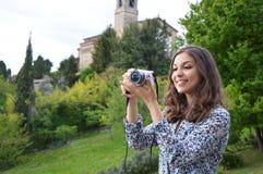 Muchacha sonriente que toma las fotos con una cámara mirrorless Fotos de archivo