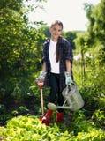 Muchacha sonriente que trabaja en el jardín con la pala y la regadera fotos de archivo