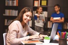 Muchacha sonriente que trabaja en el ordenador portátil Fotografía de archivo