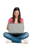 Muchacha sonriente que trabaja en la computadora portátil Imágenes de archivo libres de regalías