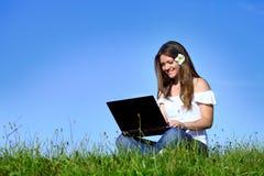 Muchacha sonriente que usa el ordenador portátil en naturaleza Imagen de archivo libre de regalías