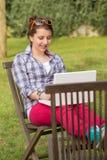 Muchacha sonriente que usa el ordenador portátil que se sienta en el parque Foto de archivo libre de regalías