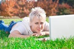 Muchacha sonriente que usa la computadora portátil Imagen de archivo libre de regalías