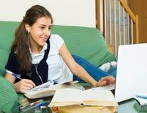 Muchacha sonriente que usa la computadora portátil Imagen de archivo