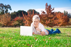 Muchacha sonriente que usa la computadora portátil al aire libre Foto de archivo libre de regalías