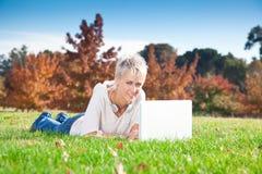 Muchacha sonriente que usa la computadora portátil al aire libre. Foto de archivo