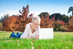Muchacha sonriente que usa la computadora portátil al aire libre. Imagen de archivo