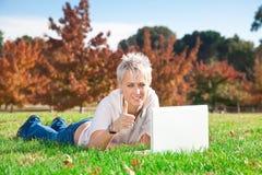Muchacha sonriente que usa la computadora portátil al aire libre Imagenes de archivo
