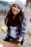 Muchacha sonriente que usa la tableta digital que se sienta en café Fotografía de archivo