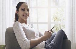 Muchacha sonriente que usa su smartphone en casa fotografía de archivo libre de regalías