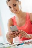Muchacha sonriente que usa su teléfono móvil Imágenes de archivo libres de regalías