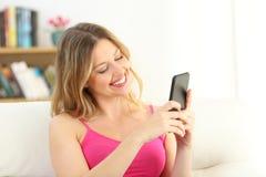 Muchacha sonriente que usa un teléfono elegante que se sienta en un sofá Fotos de archivo libres de regalías