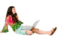 Muchacha sonriente que usa una computadora portátil y un móvil Imagen de archivo
