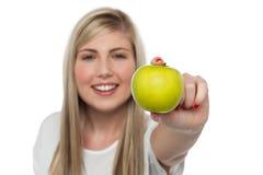 Muchacha sonriente que visualiza la manzana verde fresca a la cámara Imagen de archivo