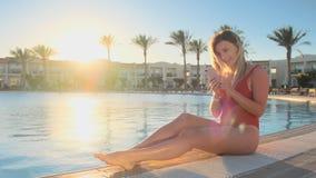 Muchacha sonriente Relaxed que se sienta cerca de lado de la piscina con un fondo del agua azul, usando un app del smartphone y m metrajes