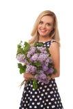 Muchacha sonriente rubia en el vestido del punto que sostiene la flor; ramo de lila fotografía de archivo