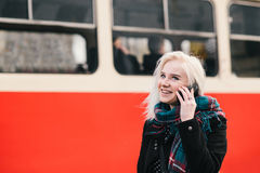 Muchacha sonriente rubia joven que habla en el teléfono en un fondo del tren rojo Retrato al aire libre de una muchacha Foto de archivo libre de regalías