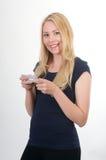 Muchacha sonriente rubia texting Imagenes de archivo