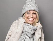 Muchacha sonriente 20s que permanece caliente en el embalaje de la bufanda acogedora del invierno Imagen de archivo