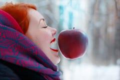 Muchacha sonriente y colgante en manzana roja grande del aire Imagen de archivo libre de regalías