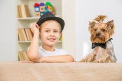 Muchacha sonriente y su animal doméstico que se inclinan en el sofá Imagen de archivo