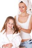 Muchacha sonriente y su pelo que aplica con brocha de la madre imágenes de archivo libres de regalías