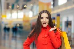 Muchacha sorprendente en compras rojas de la capa en una alameda Imágenes de archivo libres de regalías