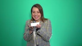 Muchacha sorprendente feliz sorprendida por el regalo aislado en fondo verde almacen de video