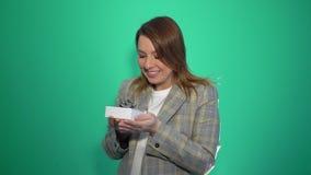 Muchacha sorprendente feliz sorprendida por el regalo aislado en fondo verde metrajes