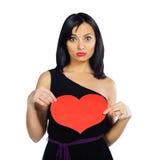 Muchacha sorprendida con el corazón rojo de la tarjeta del día de San Valentín aislado en blanco Fotografía de archivo libre de regalías