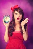 Muchacha sorprendida con el despertador Imagen de archivo libre de regalías