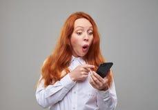 Muchacha sorprendida con el pelo castaño que señala en el teléfono Fotos de archivo libres de regalías
