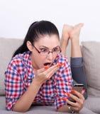 Muchacha sorprendida con el teléfono móvil en el sofá Imagen de archivo