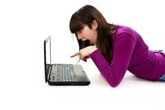 Muchacha sorprendida con la computadora portátil. El señalar en él Fotografía de archivo libre de regalías