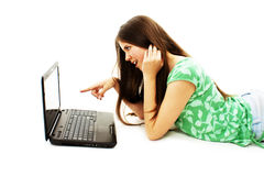 Muchacha sorprendida con la computadora portátil. El señalar en él Fotos de archivo libres de regalías