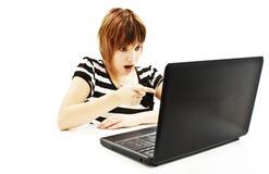 Muchacha sorprendida con la computadora portátil. El señalar en él Imagen de archivo