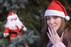 Muchacha sorprendida con la muñeca de Santa fotografía de archivo libre de regalías
